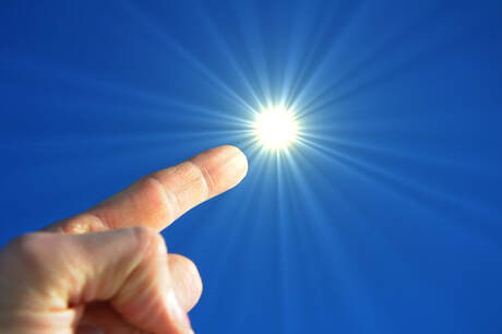 A finger pointing in the sky toward the sun as if to signify a bright idea such as free electricity.