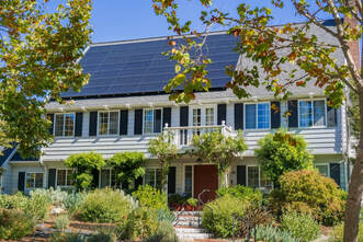 Solar panels on the front of a beautiful white 2-story colonial home in the heart of East Sacramento.