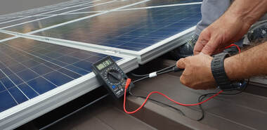 A close up shot of a solar technician using a voltage meter to test the current on a new solar panel on the roof of a modern barn just outside of Davis, CA.