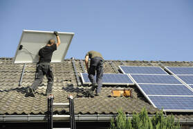 Two solar installers putting solar panels on their mounting racks on a grey Spanish tile roof in Sacramento.